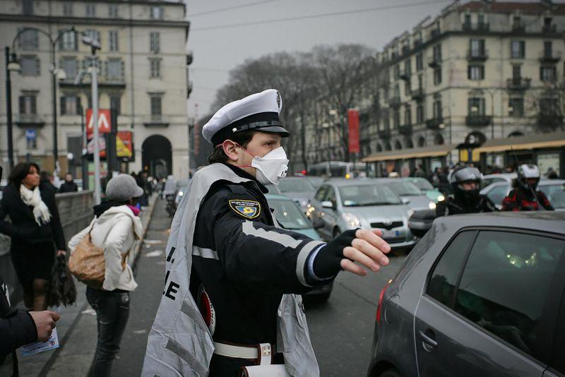Torino, İtalya'da kirli hava maskesi takan polis. Bir İklim değişikliği etkisi.