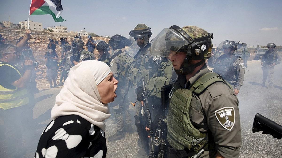 Filistinli bir kadın Batı Şeria'da bir İsrail sınır polisiyle tartışıyor.